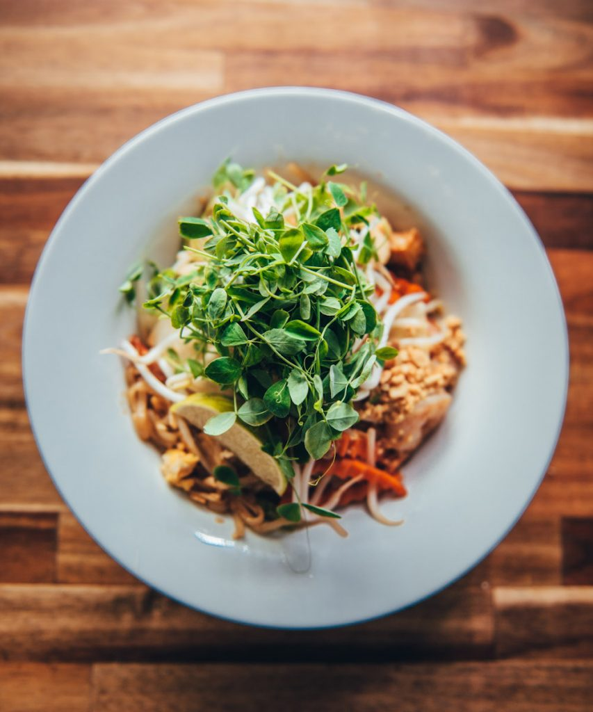 Bowl of pad thai topped with pea shoots